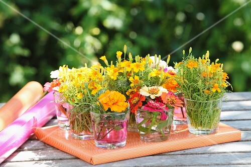 Many posies of garden flowers in drinking glasses arranged on top of wrapped gift