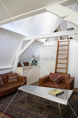 Cognac leather seating in living room with ladder leading to gallery in roof space