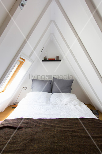 Bedroom in narrow gable room with steeply sloping ceiling