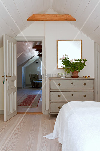 Chest of drawers next to panelled bedroom door in attic