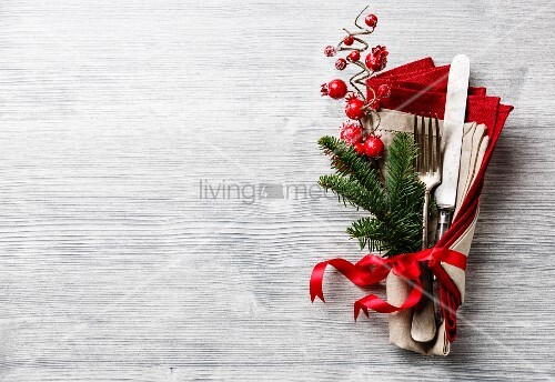 Table fork and knife set with napkin, christmas fir branch, red berries and ribbon on gray wooden background