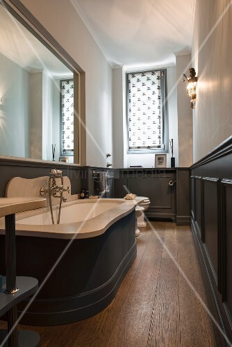Wainscoting and large mirror in narrow bathroom