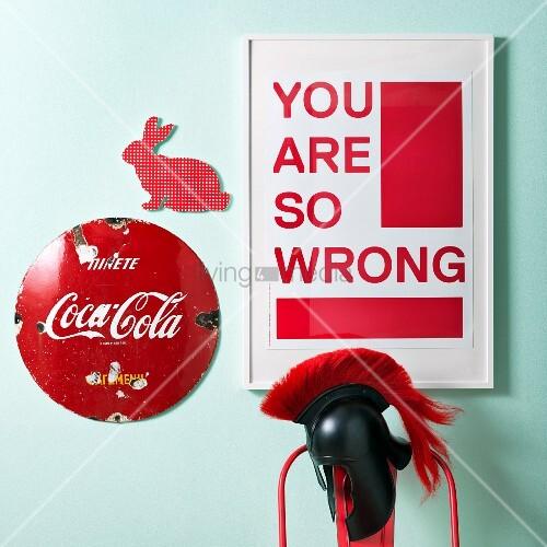 Weisser Bilderrahmen mit rotem Schriftdruck neben rotem Hasenmotiv und Vintage Werbeschild