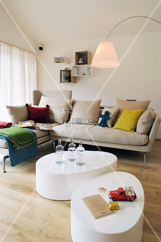 Two organically formed coffee tables in front of oatmeal sofa with colourful scatter cushions