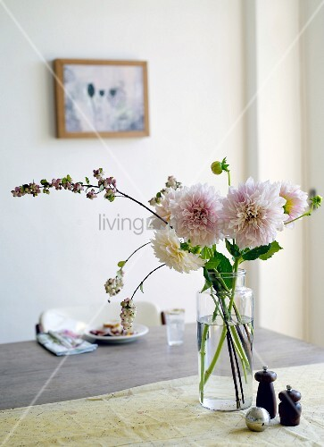Cut flowers in glass vase on table next to salt and pepper pots