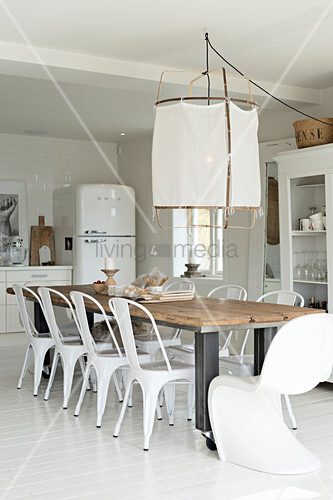 Long dining table and white chairs in open-plan kitchen
