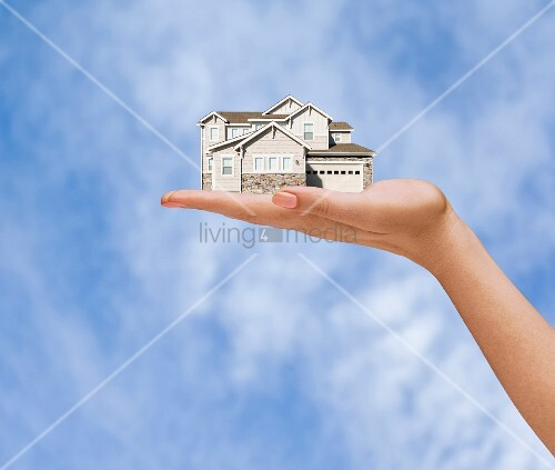 Hand of woman holding model house against sky