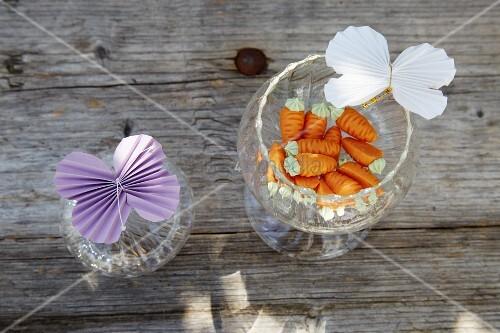 Schmetterlinge aus gefaltetem Papier an Gläsern mit Zuckerkarotten