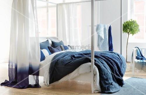 Weisse Himmelbett Mit Bettwäsche Und Vorhang In Blau Und Weiss In Hellem  Schlafzimmer