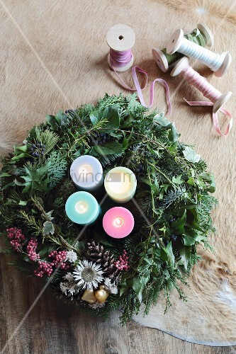 Advent wreath with four colourful candles next to ribbons