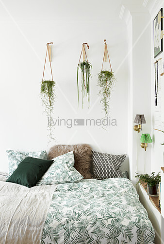 Plant hangers above bed with leaf-patterned bed linen