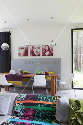 Blick über Sofa mit buntem Plaid auf Essbereich mit grauer Sitzbank und Mona-Lisa-Canvas