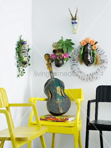 Various ethnic animal masks decorated with flowers above ethnic guitar on yellow armchair