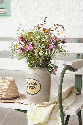 Bouquet of wild cow parsley, red campion and buttercups in stone jar on garden bench