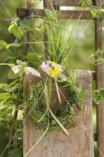 Kranz aus Gräsern mit Kuckucksblüten, Wiesenkerbel und Hahnenfuss, am Holzzaun
