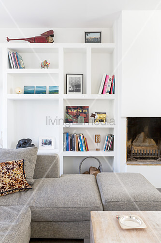 View across sofa to fitted shelving next to fireplace