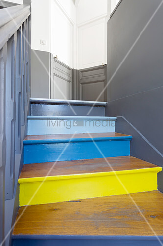 Old wooden staircase with brightly painted risers and bicoloured walls and doors