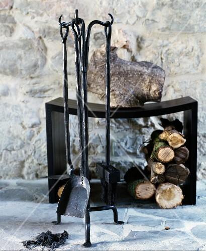 Firewood below black modern stool behind rustic set of fire irons