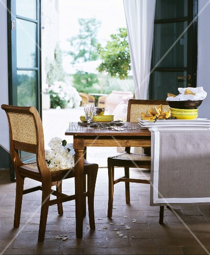Crockery and cutlery on dining table and white roses on cane chair in front of open terrace doors