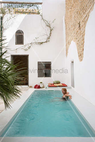 Woman relaxing in swimming pool in front of partially rendered stone wall