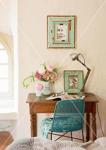 Lamp, photo and vase of flowers on antique desk