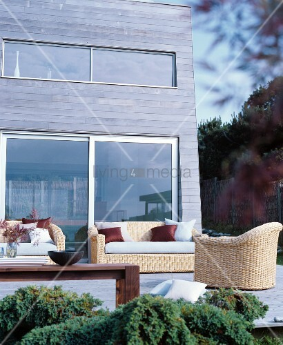 Comfortable wicker furniture on wooden terrace adjoining wood-clad façade