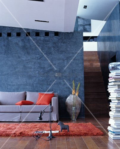 Grey, loose-covered sofa with orange scatter cushions against grey-blue stucco lustro wall with stacked books and staircase to one side