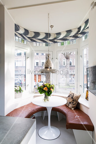 Semicircular leather bench in window bay with view of terraces houses