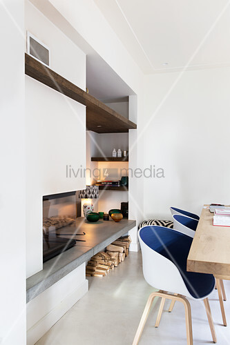 Modern shell chairs with blue seats in front of fireplace with shelves