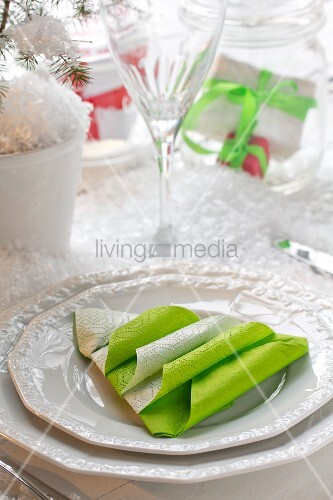 Serviettes folded into Christmas tree shape on white plate
