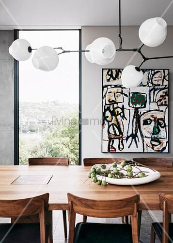 Designerleuchte überm Esstisch aus Holz vorm vertikalen Fenster