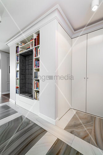 Upholstered niche surrounded by bookshelves in hall