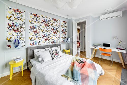 Schmetterling-Tapete überm Bett im Schlafzimmer mit Schreibtisch