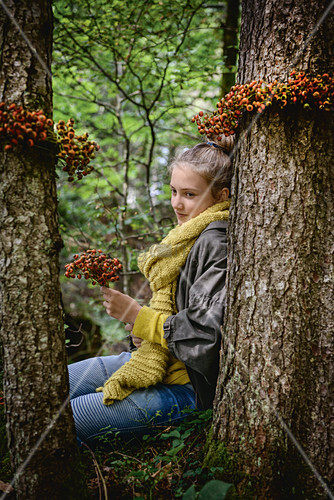 Girl in woods with wreaths of rose hips