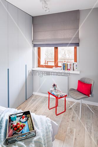 Stuhl und Beistelltisch am Fenster im Schlafzimmer in Grautönen