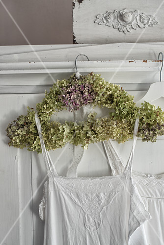 Antique nightie hung from coat hanger wrapped in hydrangea flowers