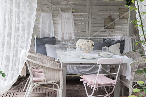 Vintage-style decoration in white wooden pavilion with seating area