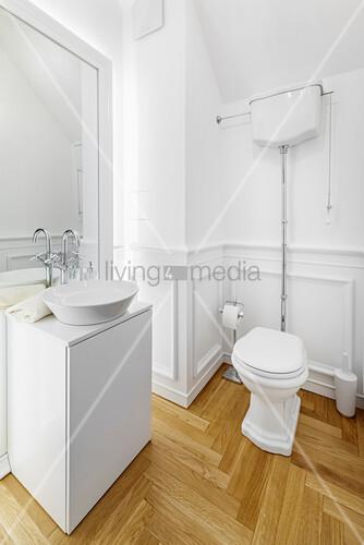 Waschtisch und Toilette in weißem Badezimmer mit Parkettboden