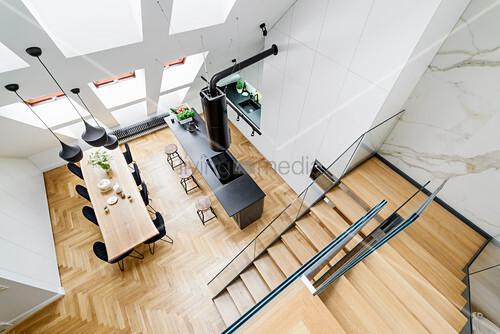 Blick auf Kücheninsel, Essbereich und Treppenaufgang in hohem Raum mit Dachschräge