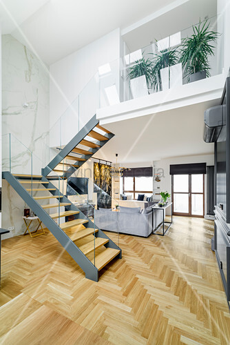 Staircase with glass balustrade and marble wall in high-ceilinged room with lounge area in background
