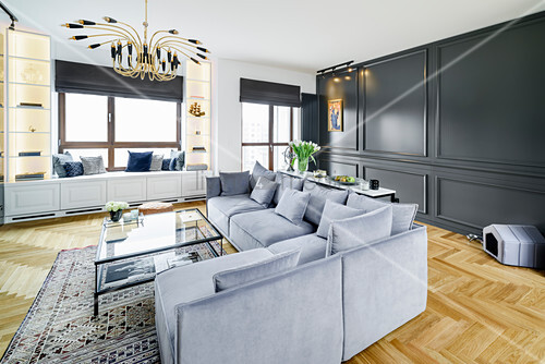 Sofa set, glass coffee table and dark, panelled wall in elegant interior
