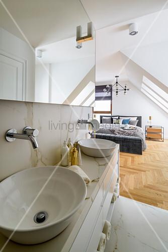Waschtisch aus Marmor mit Aufsatzbecken, im Hintergrund Schlafzimmer