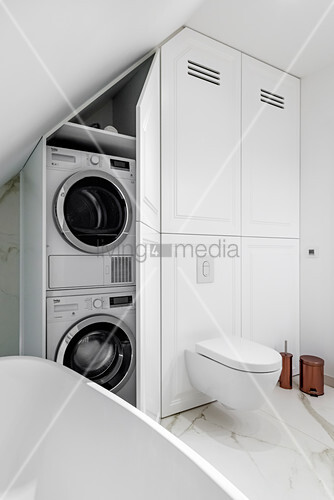 Washing machine and tumble dryer in fitted cupboard in elegant bathroom