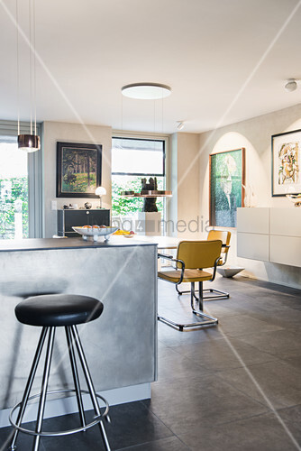 Breakfast bar and stool with dining area and artworks on wall in background