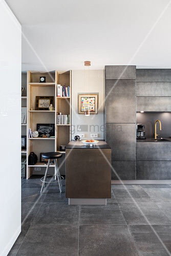 Breakfast bar used as partition between floor-to-ceiling shelving and concrete-effect kitchen