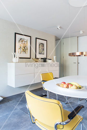 Open-plan dining area with round table, cantilever chairs, floating sideboard and artworks on wall
