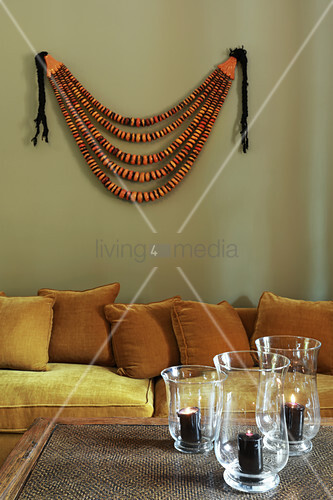 Sofa and wall hanging behind candle lanterns on coffee table
