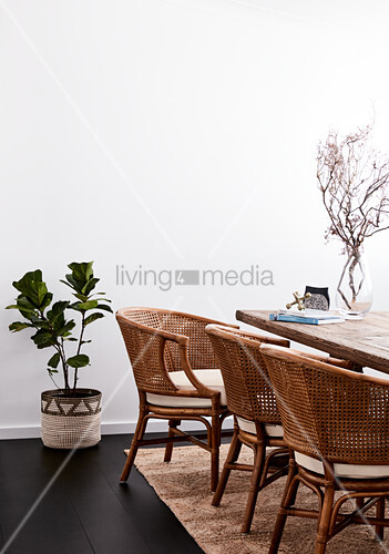 Rattan chairs around wooden table in dining room