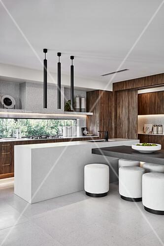 Offene Designerküche mit Theke als Raumteiler, Essbereich mit weißen Hockern