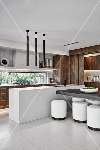 Open-plan designer kitchen with partition counter and white stools in dining area